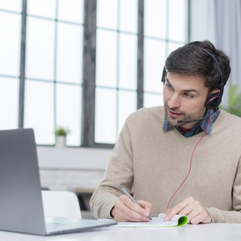 Man with a headphone following a videoconference on his laptop