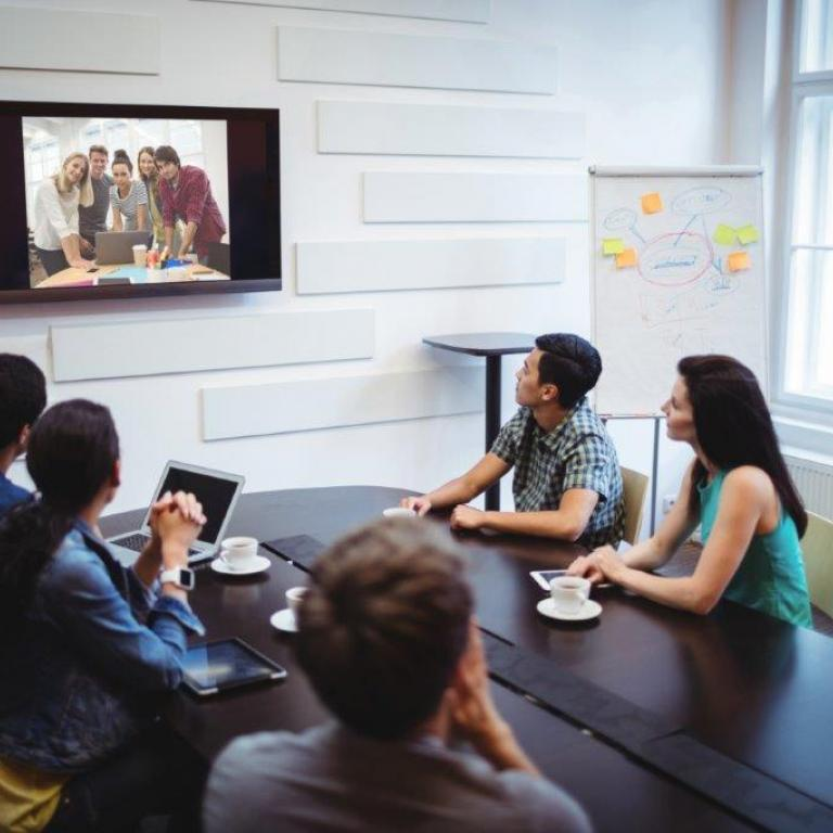 several persons using a TV-screen in a meeting room for a videoconference